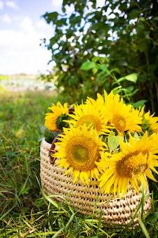 Een boeket zonnebloemen ligt in een strozak op het groene gras.