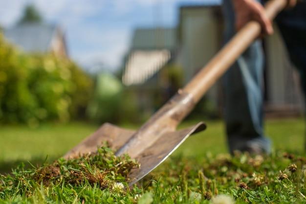 Een boer graaft met een schop de grond in de tuin. het schopblad staat op de voorgrond en gaat de bokeh-zone in. op de voorgrond is groen gras.