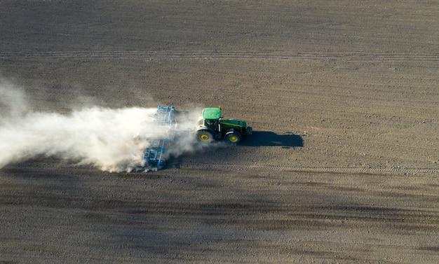 Een boer in een tractor bereidt land voor met een zaaibedrijf als onderdeel van het voorzaaiwerk aan het begin van het landbouwseizoen in de lente op landbouwgrond.