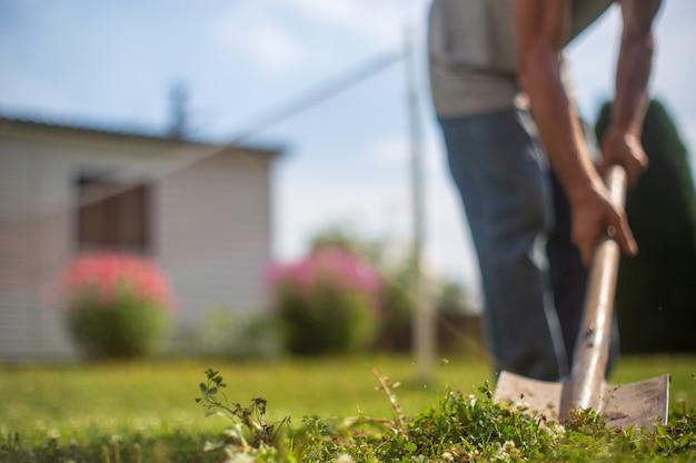 Een boer met een schop graaft de grond in de tuin