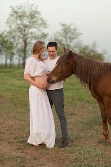 Een boer met zijn zwangere vrouw bij zonsondergang op zijn boerderij. poseren met een paard.