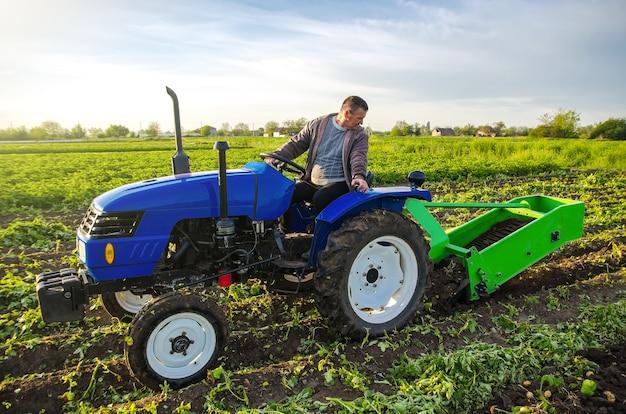 Een boer op een tractor graaft aardappelen met een graafmachine het gebruik van moderne technologie op de boerderij