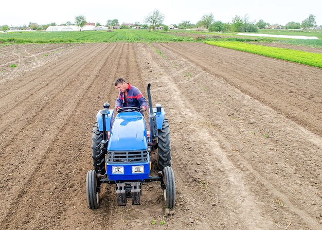 Een boer op een tractor verricht landwerk door de grond te malen en te malen grinding