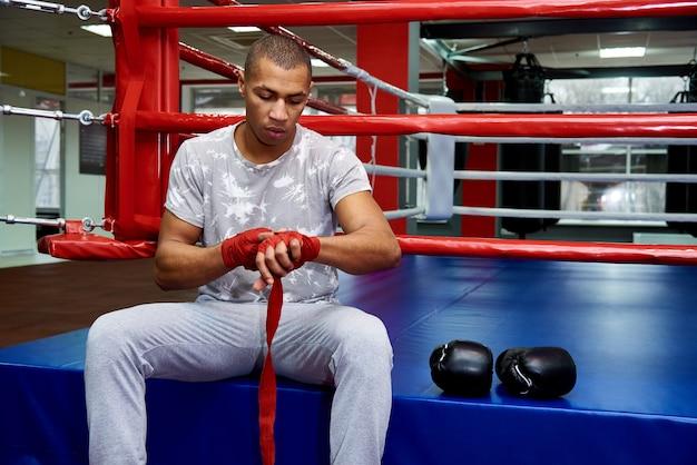 Een bokser met verbanden in zijn armen zit in de ring met bokshandschoenen.