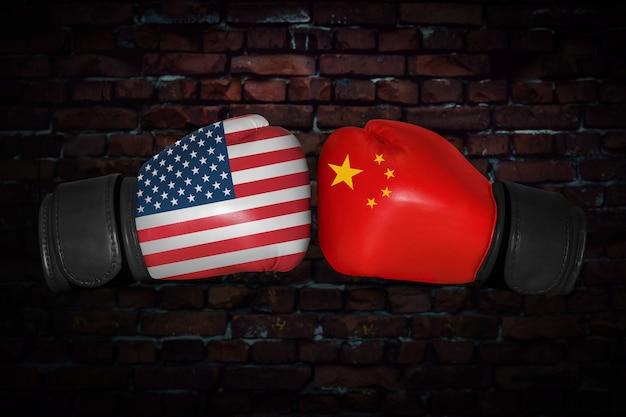 Een bokswedstrijd. confrontatie tussen de vs en china. chinese en amerikaanse nationale vlaggen op bokshandschoenen. sportcompetitie tussen de twee landen. concept van het buitenlands beleid conflict.