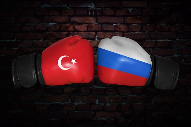 Een bokswedstrijd. confrontatie tussen turkije en rusland. russische en turkse nationale vlaggen op bokshandschoenen. sportcompetitie tussen de twee landen. concept van het buitenlands beleid conflict.