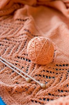 Een bol garen en een paar houten naalden liggend op de oranje gebreide plaid