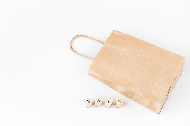 Een boodschappentas en het woord verkoop gemaakt van houten letters