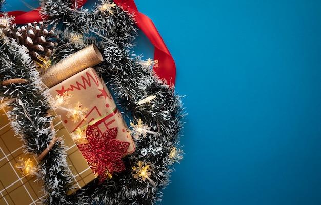 Een boodschappentas vol kerstversiering en lichtjes en een geschenkdoos met rood lint en strik