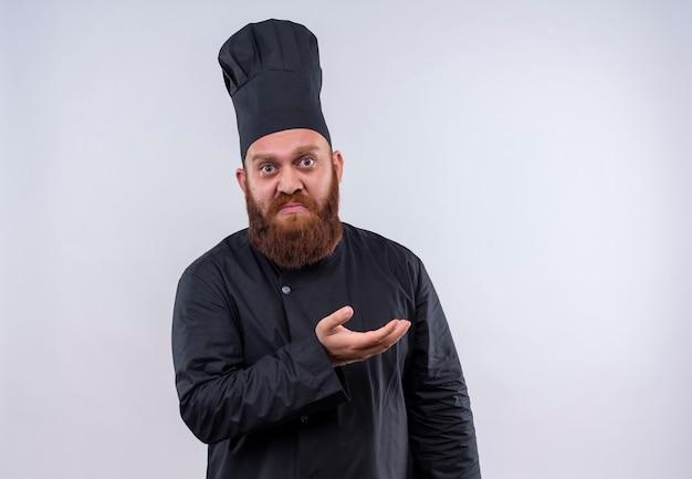 Een boos, bebaarde chef-kok man in zwart uniform hand opheffen met verbaasd gezicht op een witte muur