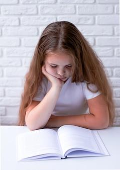 Een boos en moe schoolmeisje studeert met een boek op haar bureau.