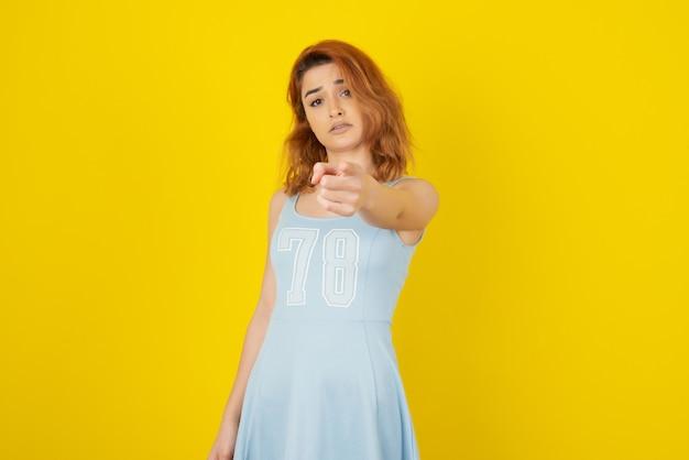 Een boos jong meisje dat met de vinger naar de camera wijst