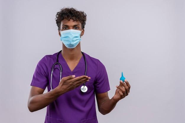 Een boos jonge knappe donkere arts met krullend haar draagt violet uniform met stethoscoop in gezichtsmasker met een klysma