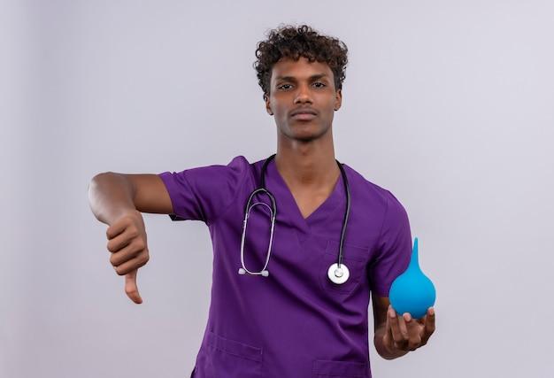 Een boos jonge knappe donkere arts met krullend haar draagt violet uniform met stethoscoop toont duimen naar beneden terwijl hij een klysma vasthoudt