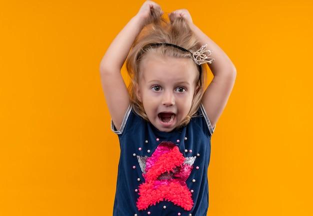 Een boos mooi klein meisje dat een marineblauw overhemd in een kroonhoofdband draagt en haar haar aanraakt met de handen op een oranje muur