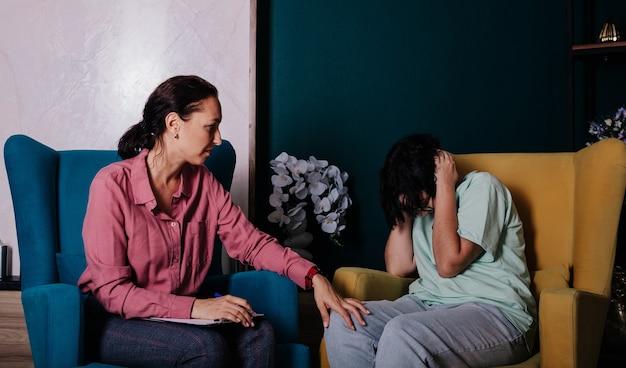Een boos tienermeisje zit in een stoel op een afspraak van een psycholoog met een vrouw. tiener problemen