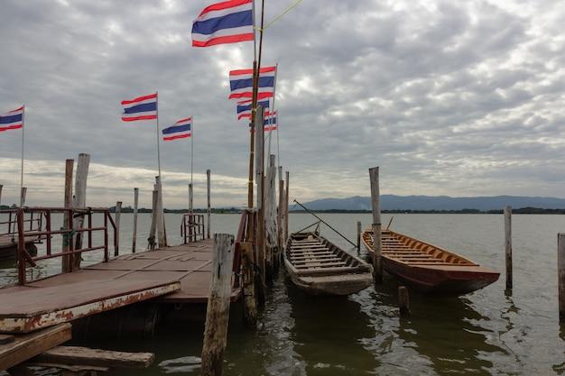 Een boot die aan een houten pijler op de rivier en de vlag van thailand in kwan phaya, thailand wordt gebonden