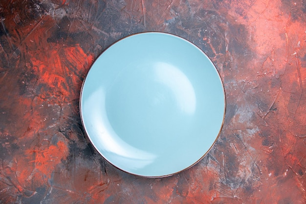 Een bord blauw rond bord op de rood-blauwe tafel