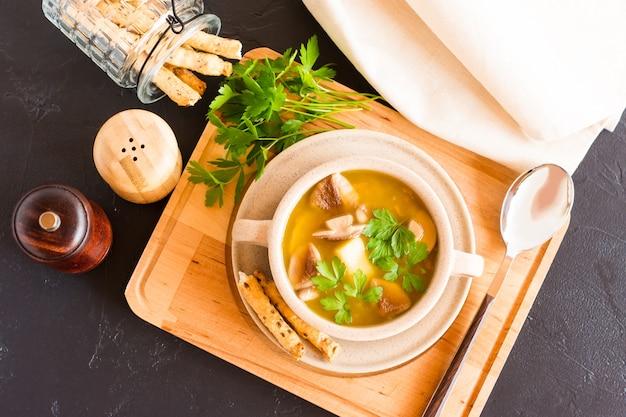 Een bord boschampignonsoep op een houten standaard met peterselie en soepstengels. bovenaanzicht.