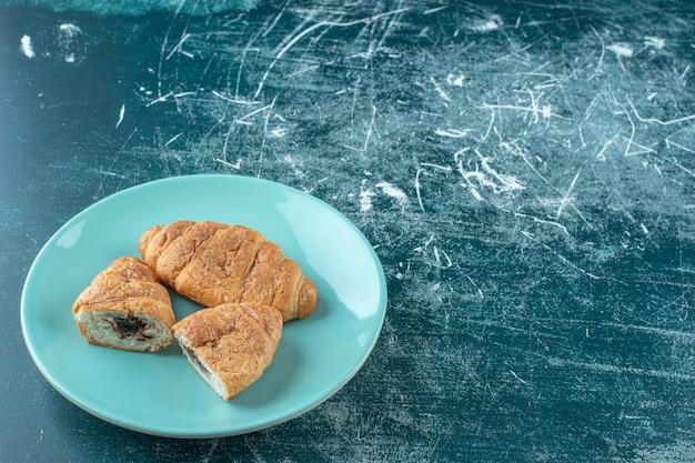 Een bord croissants, op de blauwe tafel.