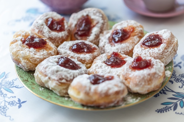Een bord donuts gevuld met jam en bedekt met suiker.