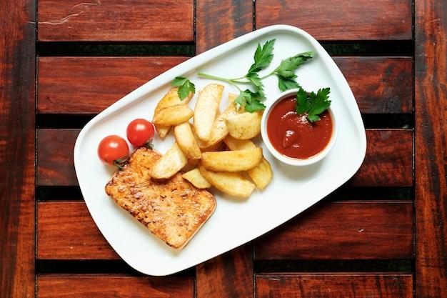 Een bord frietjes met inhaalslag, houten achtergrond