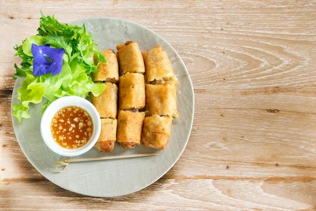 Een bord gefrituurde loempia's met zoete chili-dipsaus.
