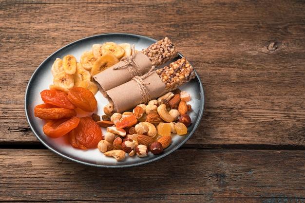 Een bord gezonde zoete snacks. gedroogde abrikozen, bananenchips, noten en mueslireep op een houten muur. zijaanzicht, kopieer ruimte.