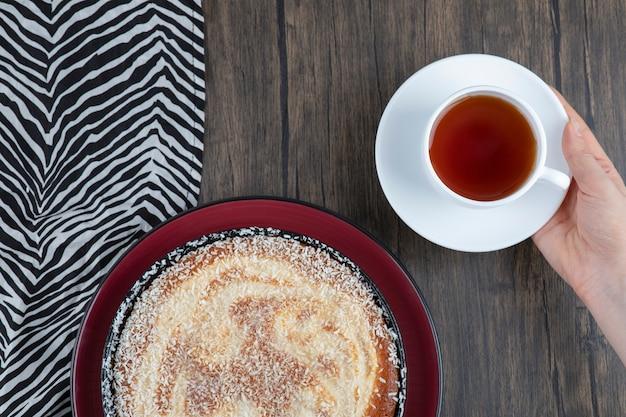Een bord heerlijke taart met een kopje zwarte thee op een houten tafel.
