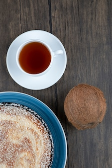 Een bord heerlijke taart met verse hele kokosnoot op een houten tafel.