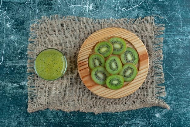Een bord kiwi slice naast kiwi smoothie op handdoek, op de marmeren tafel.