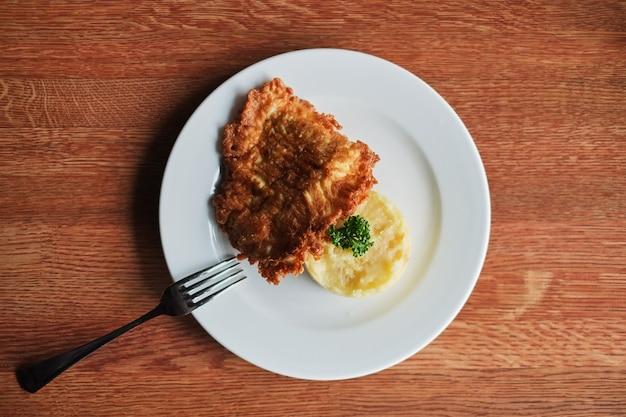 Een bord met aardappelpuree en een geroosterd ei met tomaten en een vork.