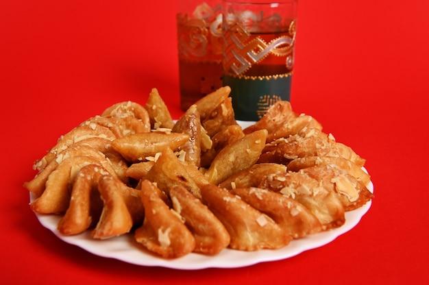 Een bord met arabisch dessert van amandelmeel en honing en twee mooie glazen met traditionele marokkaanse thee met munt op rode achtergrond. ruimte kopiëren