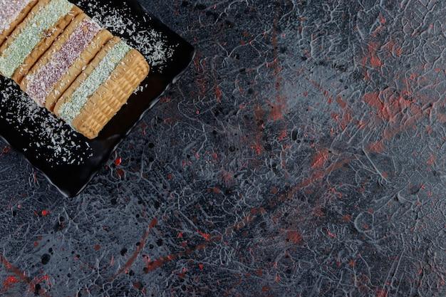 Een bord met belqian-wafels op een donkere tafel.