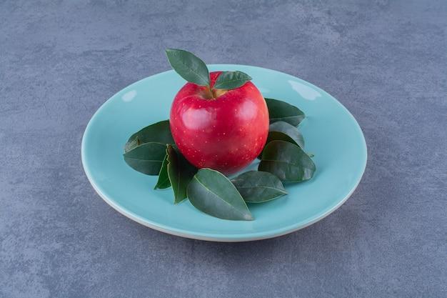 Een bord met bladeren met appel op marmeren tafel.