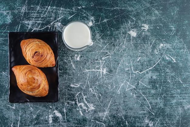 Een bord met broodjes bladerdeeg met een glazen kruik verse melk.