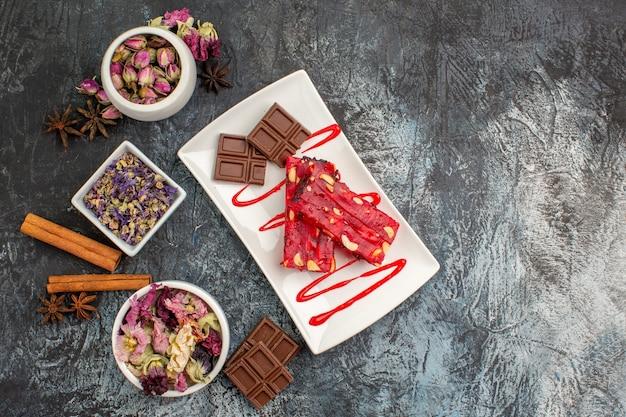 Een bord met chocolade en kommen met gedroogde bloemen eromheen op grijs