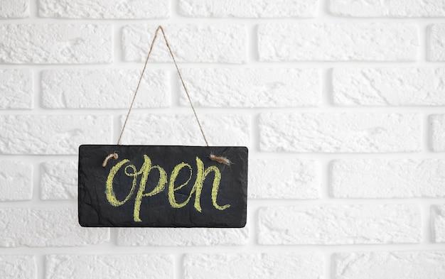 Een bord met de tekst open op café of restaurant hangt aan de deur bij de ingang. na quarantaine. bedrijfsopening