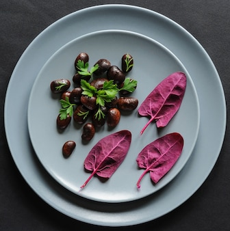 Een bord met donkere bonen en rode spinazieblaadjes