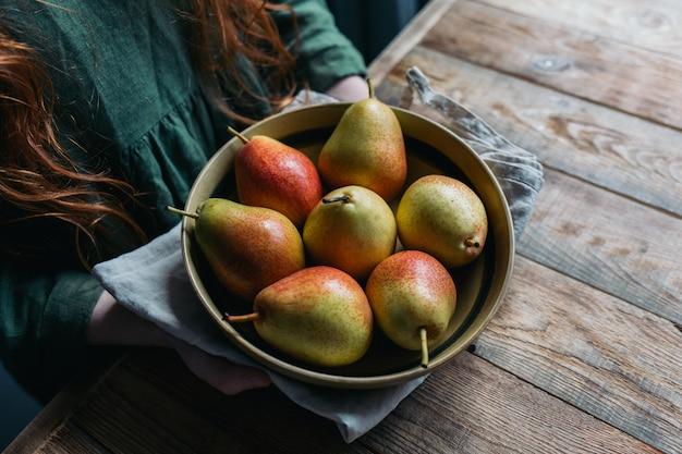 Een bord met een verse oogst van peren wordt op een houten tafel geplaatst.