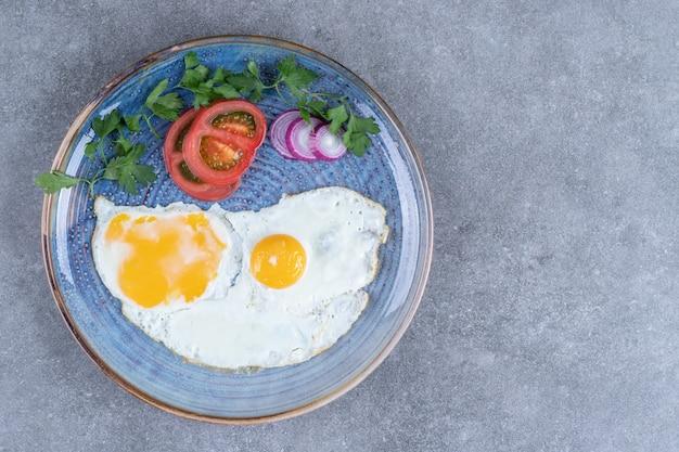 Een bord met gebakken eieren en gesneden groenten