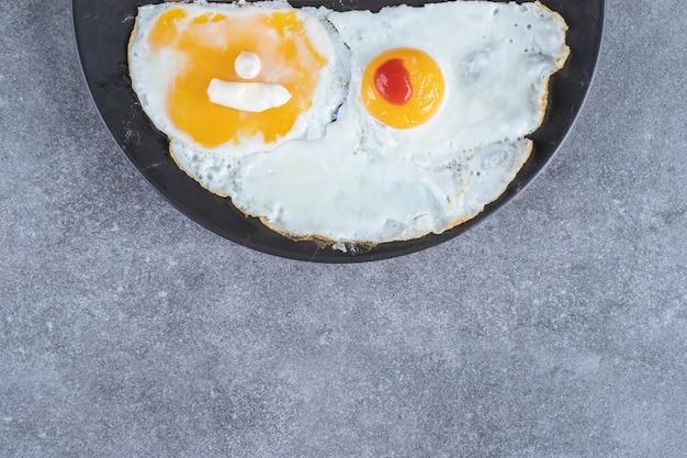 Een bord met gebakken eieren op een grijze ondergrond