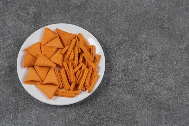Een bord met gedroogd brood en maïschips op het marmeren oppervlak