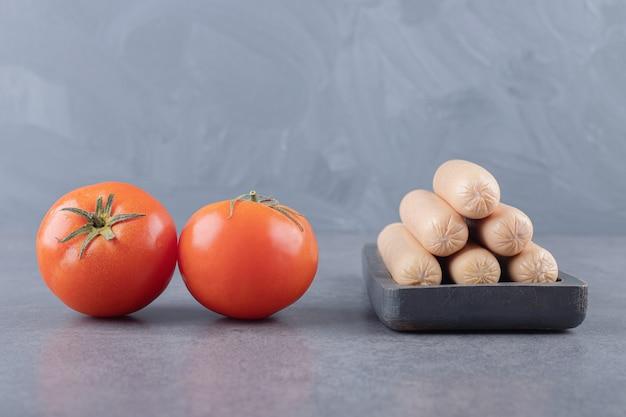 Een bord met gekookte worstjes en rode tomaten