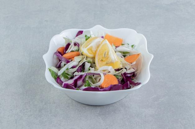 Een bord met geraspte groenten met citroen, op de marmeren achtergrond.