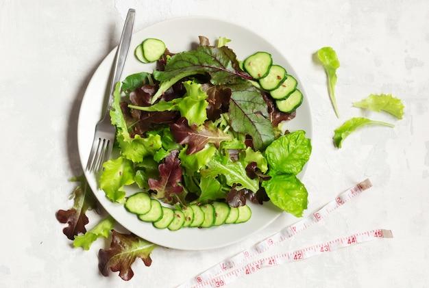 Een bord met groene slablaadjes, sesamzaadjes en plakjes komkommer, links een meetlint en rechts een vork