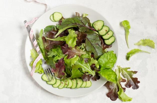 Een bord met groene slablaadjes, sesamzaadjes en plakjes komkommer, links een meetlint om een vork gewikkeld