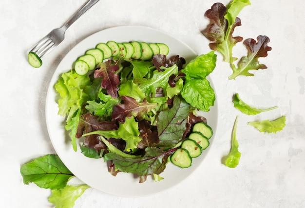 Een bord met groene slablaadjes, sesamzaadjes en plakjes komkommer, links een vork