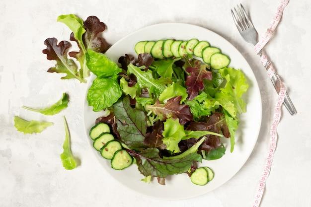 Een bord met groene slablaadjes, sesamzaadjes en plakjes komkommer, rechts een meetlint om een vork gewikkeld