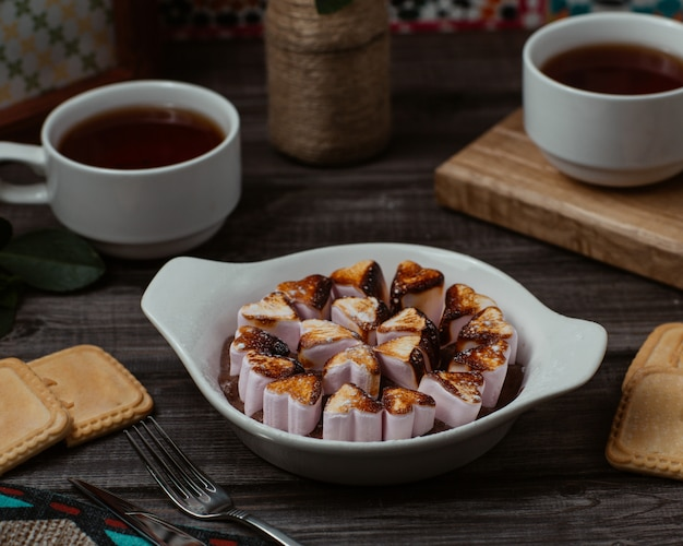Een bord met hartvormige vanille choco koekjes, koekjes met kopjes thee